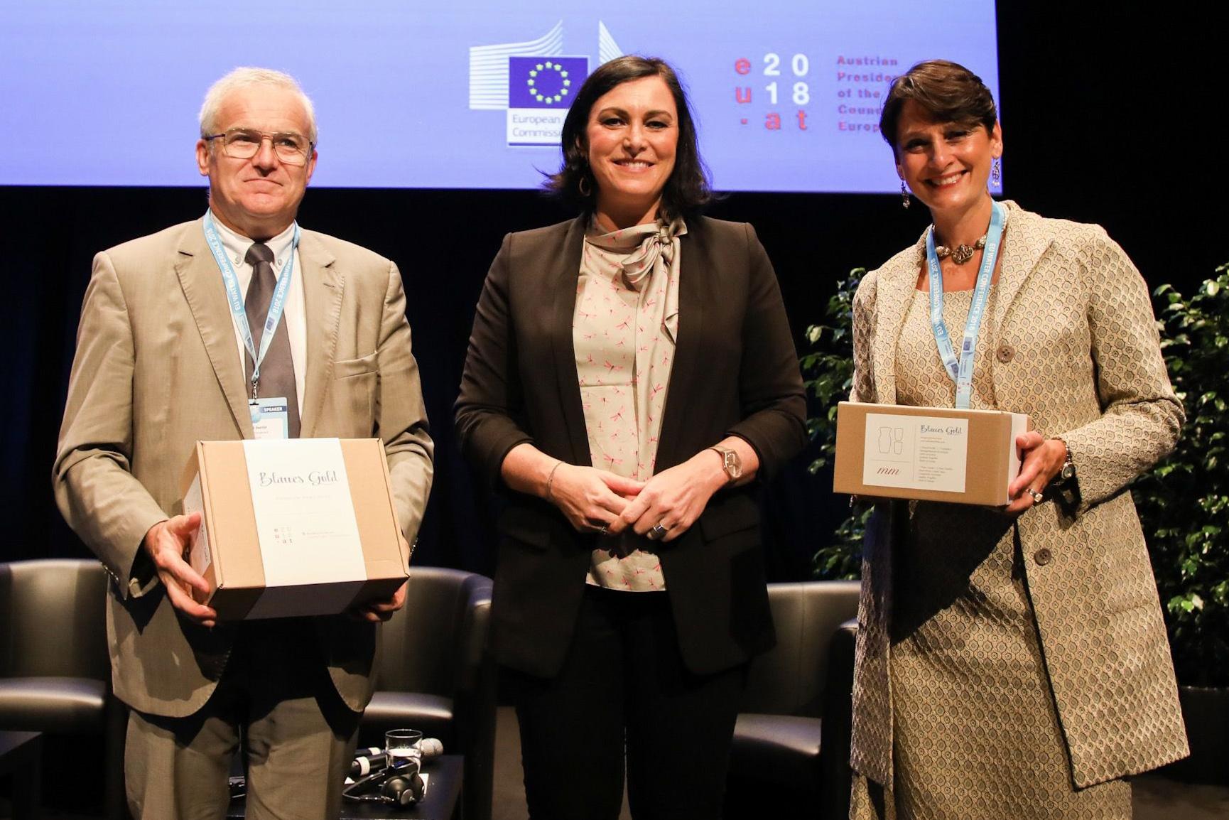 """Bundesministerin Elisabeth Köstinger mit Veronica Manfredi (EU Kommission) und Michel Dantin (EU Parlament), mit je einem Wasserkrug-Set """"Europa"""" als Gastgeschenk."""