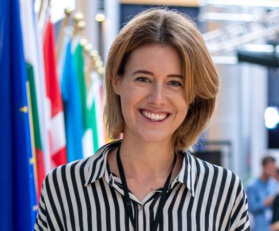 EU-Parlamentsabgeordnete  Claudia Gamon lächelnd vor Flaggen