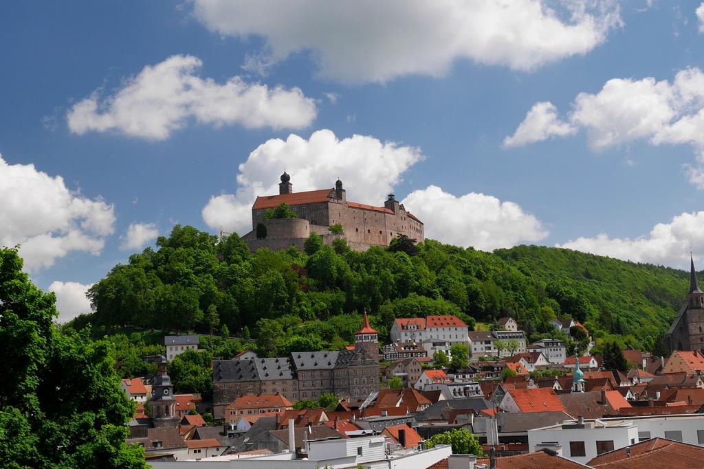Landschaft mit Hügel und Burg darauf sowie Dort im Tal davor