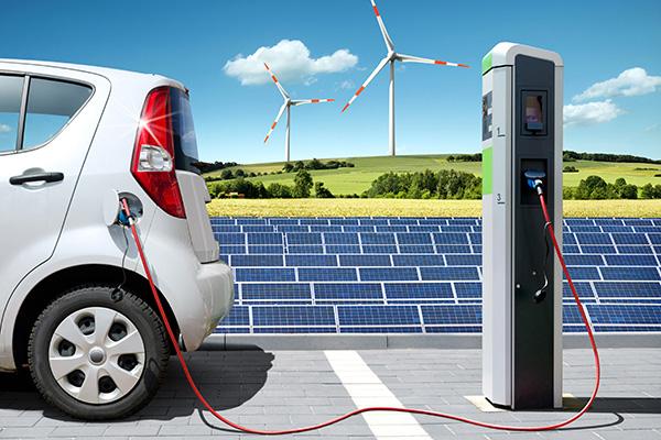Auto an Ladestation mit Solarpaneelen und WIndrädern im Hintergrund